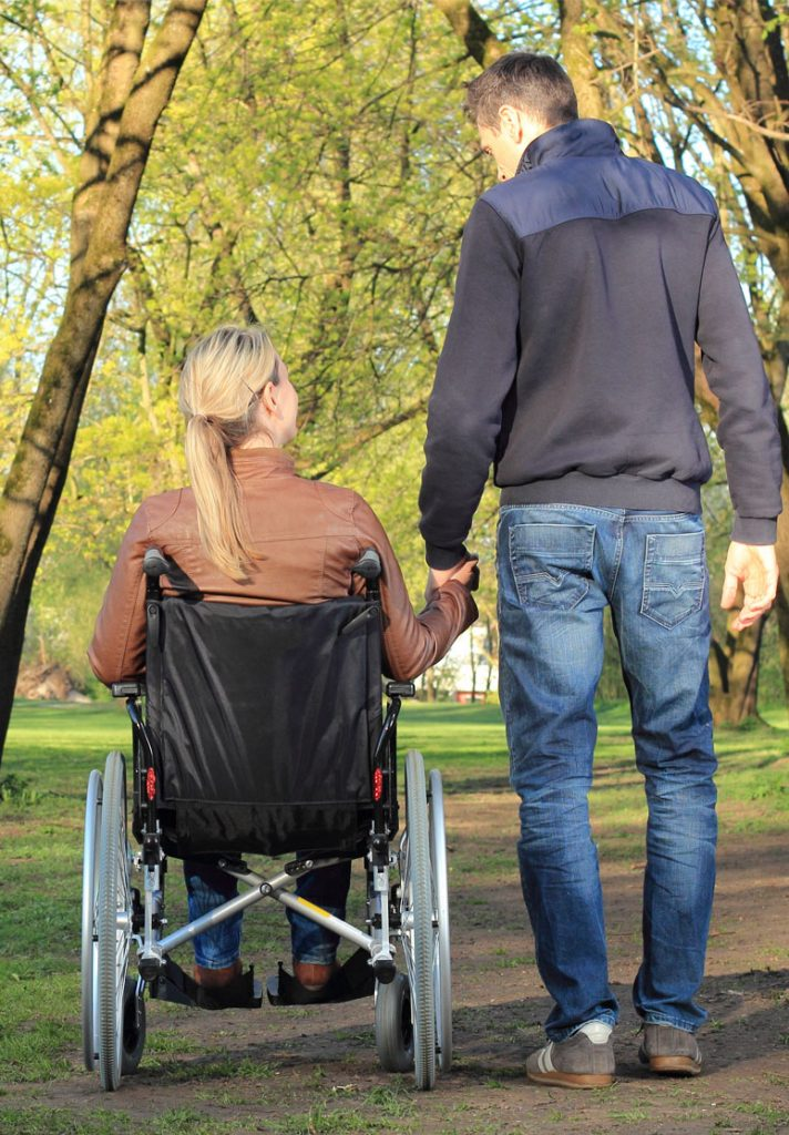 Man walking with woman in wheelchair: Help Stoke Survivors & Caregivers | Stroke Recovery Foundation